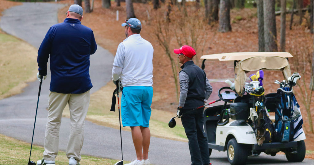 golfers wait on the tee